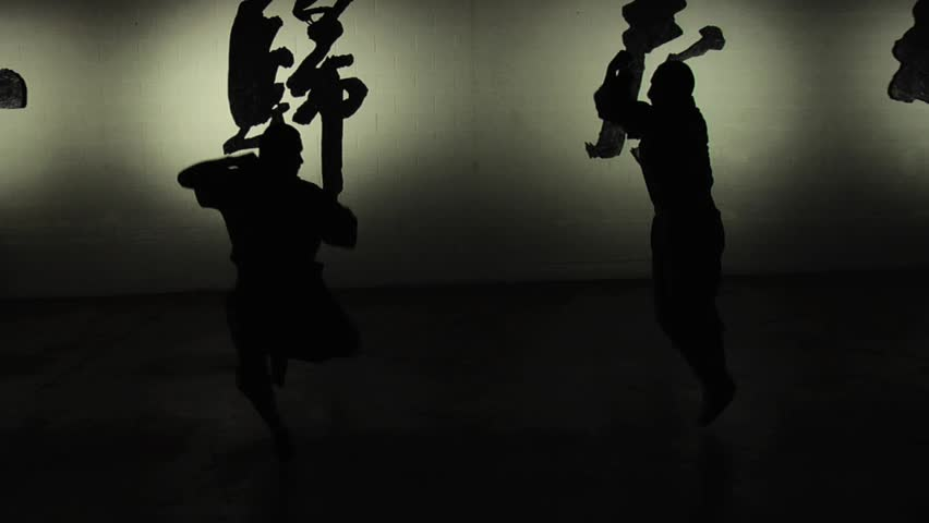 Two Shaolin monks demonstrate in silhouette their ancient form of kung fu. Shot in slow motion.