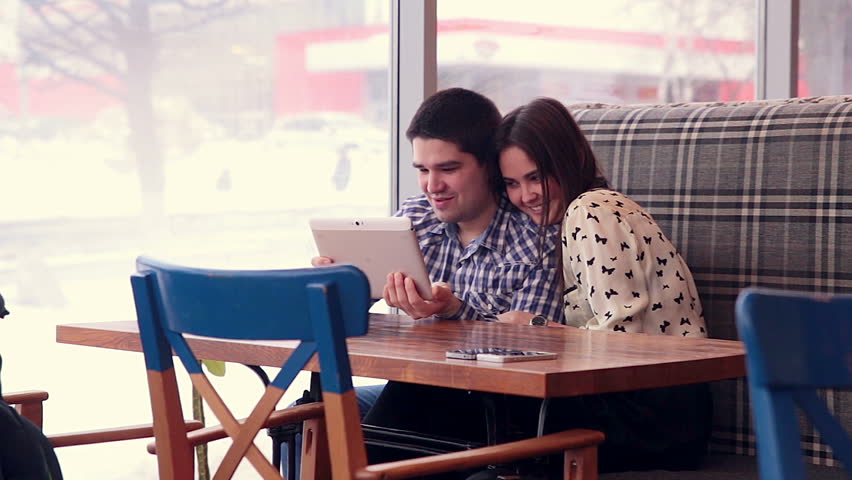 Couple sitting on sofa, using tablet. | Shutterstock HD Video #23470156