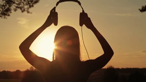 Silhouette of woman putting on the headphones, listening to music and dancing in the forest. Sunset light, sun lens flares, golden hour. Relax, nature and joyful concept