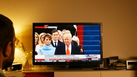 PARIS, FRANCE - JAN 20, 2017 Happy Man saluting welcomes watching TV news reporting 45th U.S. President inauguration ceremony - President Donald Trump on inaugural platform - Senator Roy Blunt speech