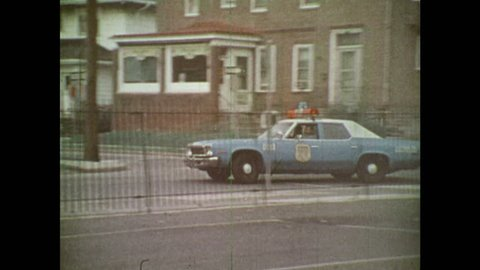 UNITED STATES 1970s: Police car drives into parking lot. Boy runs. Police car stops. Policeman runs after boy. Boy leaves parking lot. Boy runs. Police men leaves parking lot.