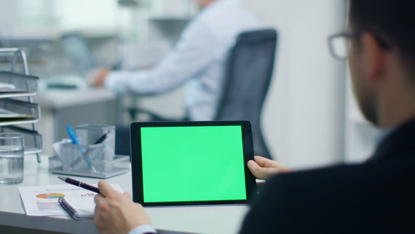 Close-up of a Businessman Working on a Tablet Computer with Green Screen, Holding Pen. His Colleague Works in the Background. Office is Light and Modern. Shot on RED Cinema Camera 4K (UHD). | Shutterstock HD Video #23570836