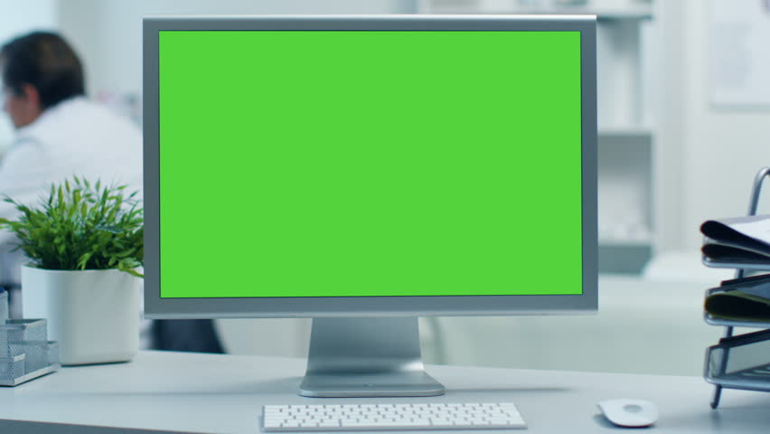 Close-up of a Monitor with Green Screen. Doctor Working at his Desk in the Background. Shot in a Modern Medical Office. Shot on RED Cinema Camera 4K (UHD).