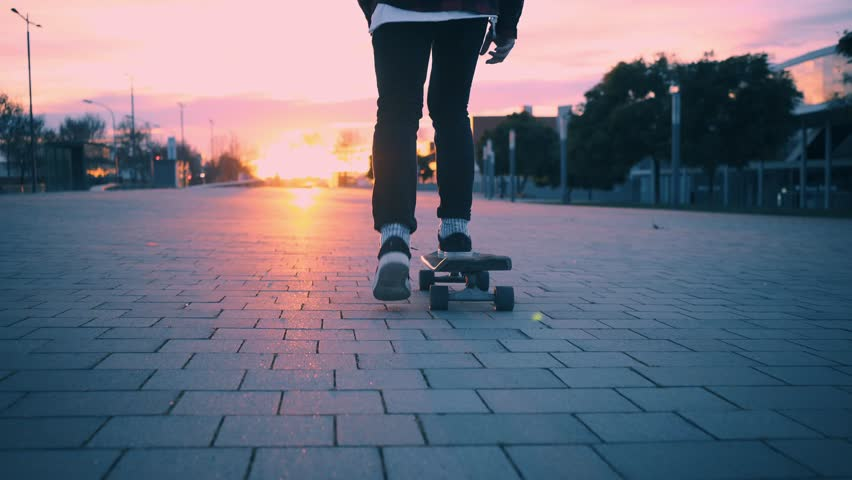 Beutiful and soft pink pastel lighning at winter time. Following camera with close up on skater legs, skating his longboard in city street into sunset
