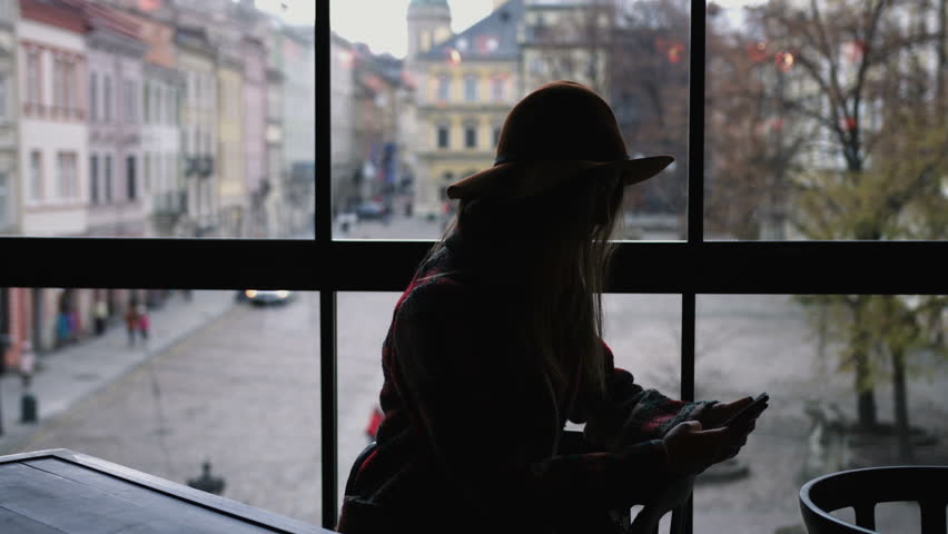 Silhouette of woman use mobile phone in city cafe at sunset on blurred architecture and road background. 4k   Shutterstock HD Video #23586106