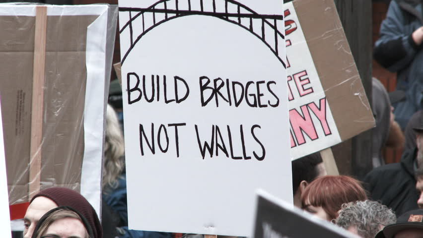 PORTLAND, OREGON - CIRCA 2017: People gather at rally holding signs such as Build Bridges Not Walls and We Will Not Go Quietly.