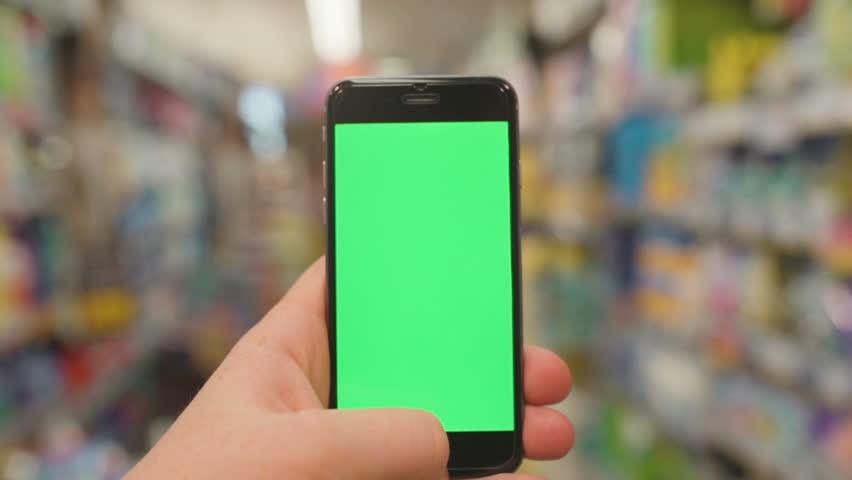 Man at Supermarket Using Smartphone with green vertical screen. Closeup. HD, 1920x1080. | Shutterstock HD Video #23597836