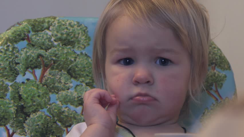 Little girl looks perplexed and bewildered, sitting in the kitchen | Shutterstock HD Video #23617876