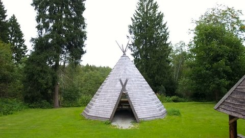 The pyramid wooden house or teepee house in the forest being surrounded with lots of pine trees