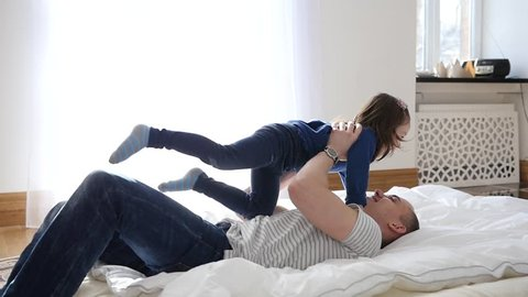 Happy Family Idyll - Little Child Daughter Jump On Father Arms And They Fall On A Bed