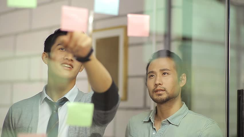 Asian corporate executives discussing business using sticky notes in office.