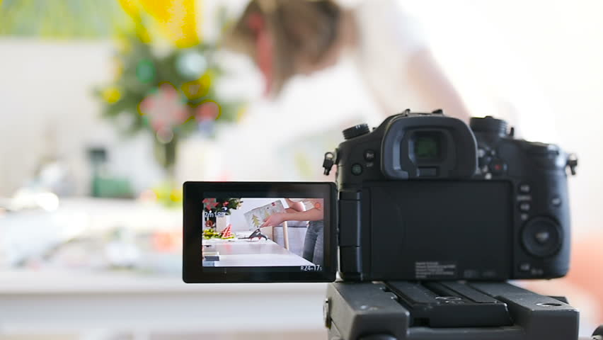 Woman preparing hand-made object with glue pistol fashion decorations gifts on table with professional video camera in the foreground filming the experience of the influencer vlogger tilt-shift