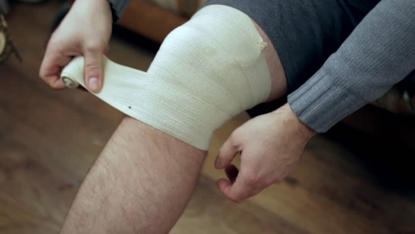 Young man wrapping his knee injury with elastic bandage closeup