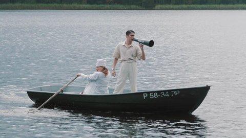 Nurse paddling boat on lake, man in hair net yelling into megaphone summer sunny day