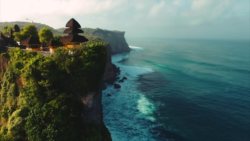 Pura Uluwatu temple. Stone cliffs, ocean waves and oceanscape. Aerial top view. Bali, Indonesia. - 4K stock footage clip