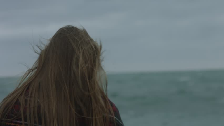 Pretty girl looks at the sea in the storm #23797186