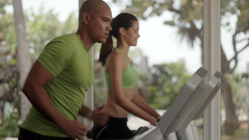 Young man and woman working out and running on treadmill in fitness club, people and sport activity