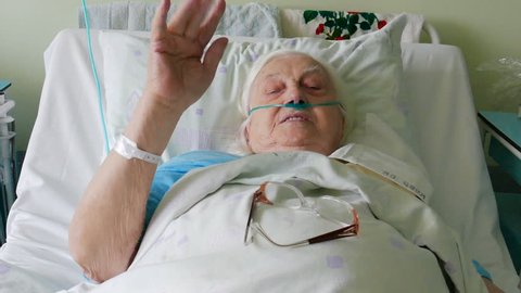 Old, ill woman in hospital bed
