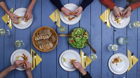 Preparation of grilled fish and fresh vegetable salad. Top view on people eating meal and drinking vine together on rustic mediterranean table setting. Long Stop motion & Timelapse shot.