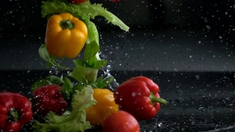 fresh vegetables falling with water in slow motion on black background
