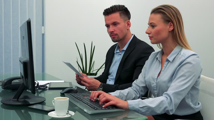 A man and a woman (both young and attractive) sit at a desk in an office, she works on a computer, he talks | Shutterstock HD Video #23864176
