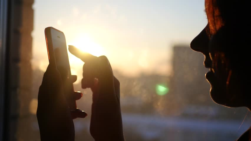 Woman uses the phone, drives a finger across the screen, peering into the gadget, standing at the window on the background of a beautiful sunset with glare, 3840x2160, 4k | Shutterstock HD Video #23891314