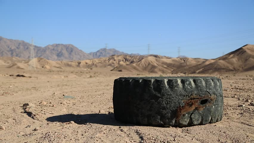 Abuse of environment. Old black tyre and other garbage in desert, environmental pollution. Big tyre lies in desert near Aqaba in Jordan   Shutterstock HD Video #23894596