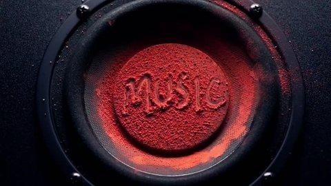 Music caption on orange powder over trembling loudspeaker. Super slow motion shot