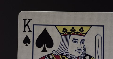 Revealing a hand of 21 in blackjack with a king and ace of spades macro / ALPHA MATTE