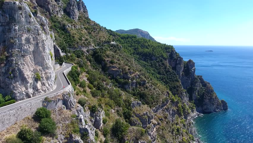 Aerial of cliff coastline road motorcycle driving over curvy sea shore road towards camera in flight beautiful Italian Mediterranean landscape amazing blue ocean for summer vacation tropical road 4k