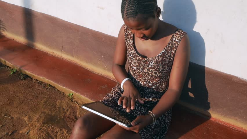 A rural South African black woman working or texting using computer tablet in village