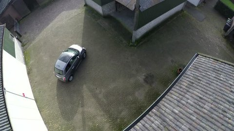 Aerial bird view from drone spying on car driving away from home then drone moving from position to follow small european car could be modern paparazzi drone stalker or surveillance quadcopter 4k