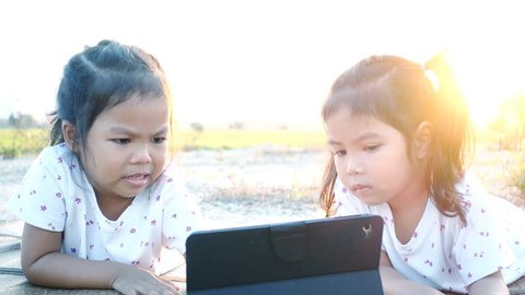 Asia little girl using pad with her sister at sunset