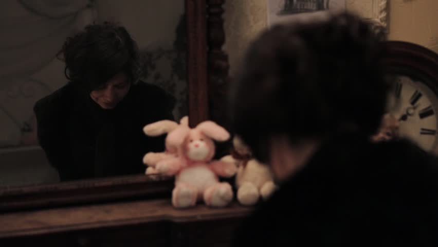 sad child looking in mirror. sad brunette woman with hair knob in black clothes crying front of reflection mirror child looking