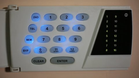Man puts the building on the alarm. It introduces a special code to put the building on the alarm. After the introduction of the code alarm lights red. Now the building is protected.