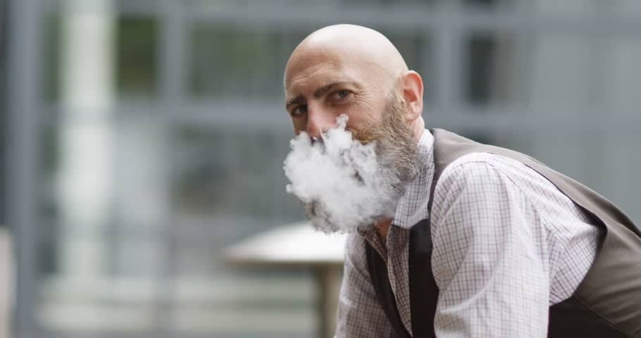 4K Close up portrait man vaping outdoors exhales cloud of smoke through his nose & turns to look at camera. Slow motion.