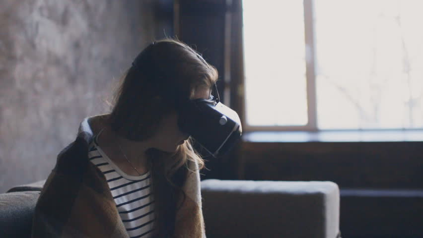 Happy young woman with virtual reality headset playing game at home | Shutterstock HD Video #24017536