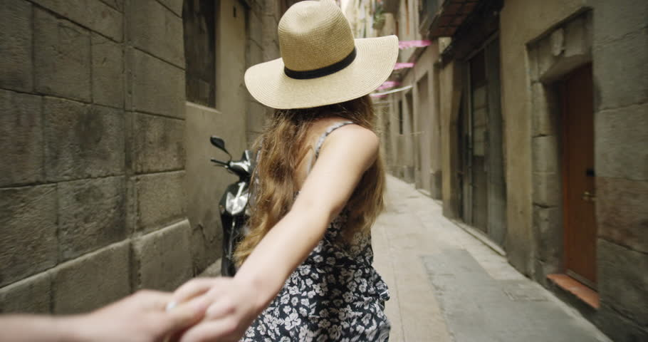 Young couple holding hands woman leading boyfriend walking down European street in Barcelona Spain POV travel concept #24044056