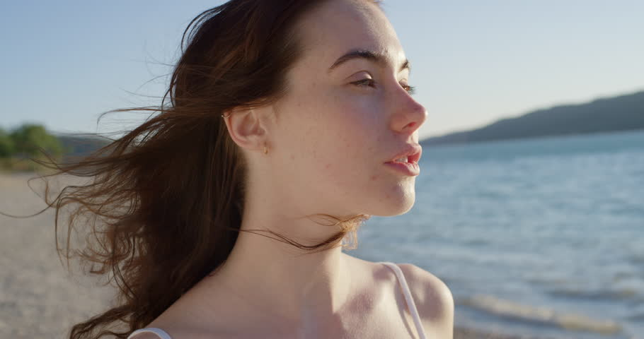 Close up portrait of beautiful young woman running hand through hair blowing in wind on tropical beach slow motion