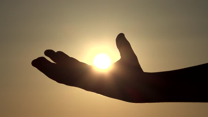 Child Hand Catching Playing Sun Rays, Beams in Fingers, Palm Silhouette