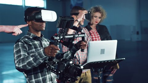 Young people testing camera gyro stabilizer gimbal with virtual reality headset on, looking around. Men and woman with laptop.
