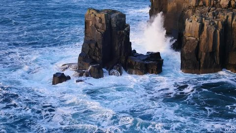 Big strong waves crashing against to  sharp rock of the Isle of Skye in Scotland. Foamy sea level. Rounded big black stones and sharp rocky tower above foamy sea of the Hebrides. Tourist resort.