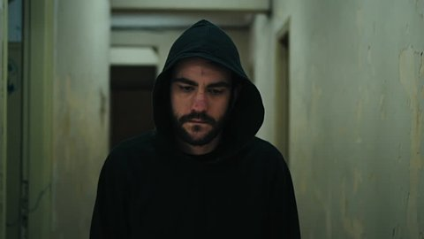.Following a hooded young man inside a dark derelict ghetto building.A hooded young man facing social issues,walking inside a big apartment building in the projects in 100fps slow motion.Camera gimbal