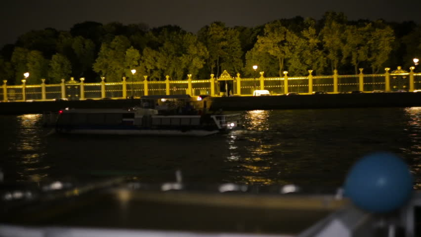 The boat goes through the channel in center St. Petersburg, shooting from floating ship. The river bus. Night.