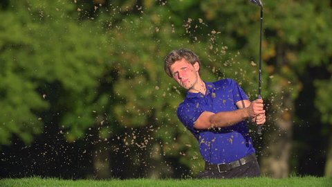 Young male golfer chips out of bunker in slow motion and celebrates