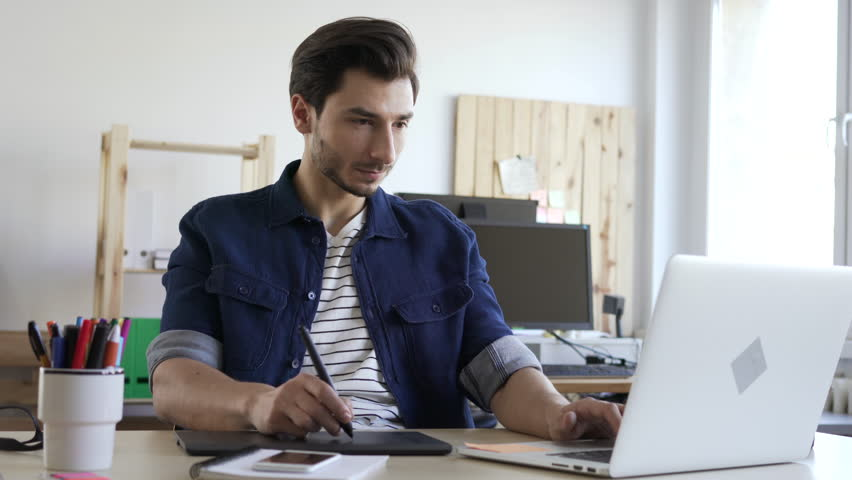Freelancer working with graphic tablet and laptop sketching new project  | Shutterstock HD Video #24164326