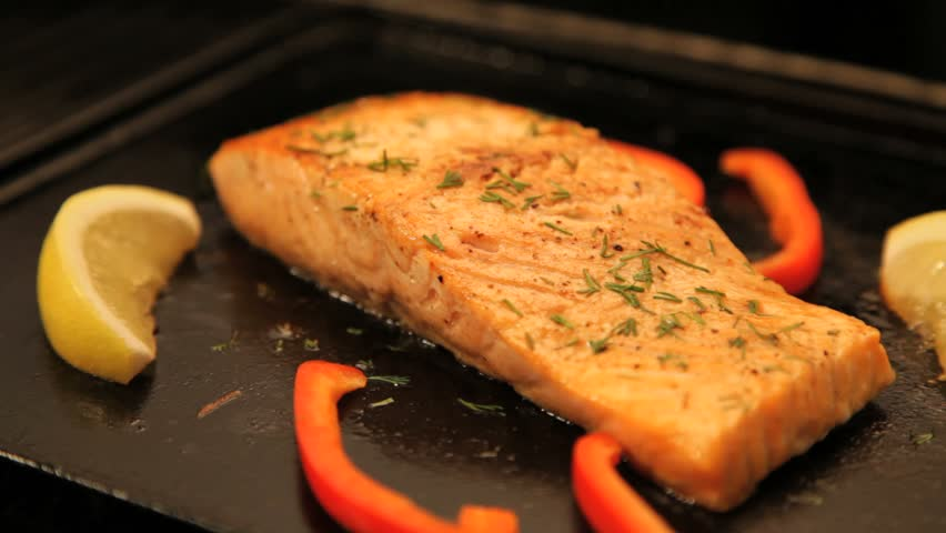 Juicy salmon fillet cooking on hot barbecue, locked down.