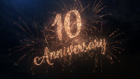 Happy birthday Anniversary 10 years celebration greeting text with particles and sparks on black night sky with colored slow motion fireworks on background, beautiful typography magic design.
