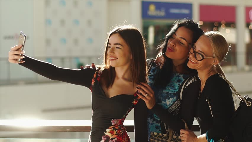 Charmed women taking selfie after shopping. Girls smiling. They posing for photos, taking their hands on hair, face and glasses. Have many colorful shopping bags. | Shutterstock HD Video #24185566