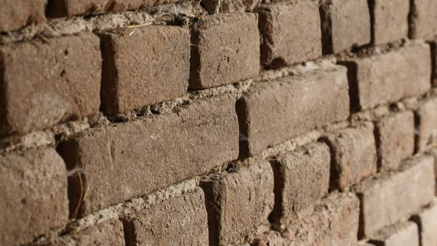 Clay bricks headers and stretchers close-up slow-tilt 4K 2160p 30fps UltraHD footage - Weathered house wall texture details shallow DOF 3840X2160 UHD tilting video